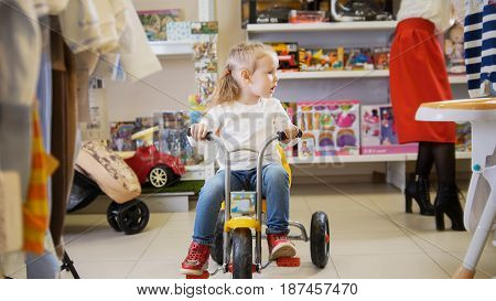 Little girl rides a tricycle at children's store.
