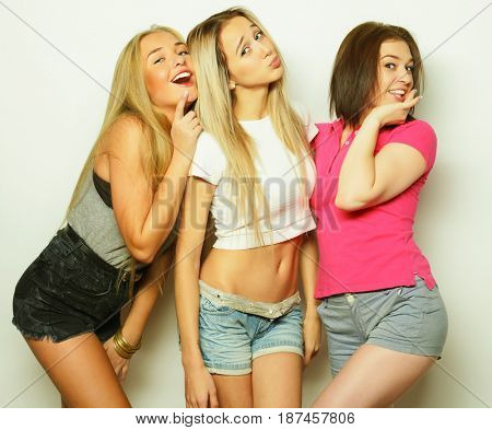 Three best friends posing in studio, wearing summer style outfit and jeans shorts. Girls smiling and having fun.