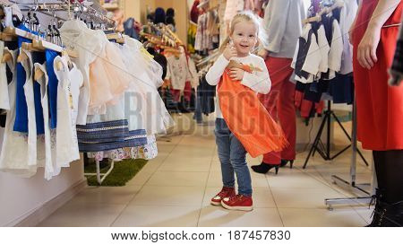 Shopping for kids - cute little girl tries on red dress in a clothing store for children