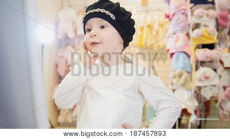 Little girl in a black beret admiring herself before a mirror in a clothing store for children.