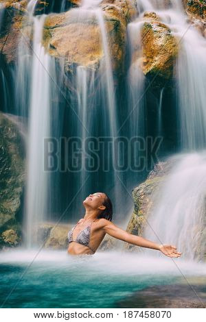 Waterfall woman meditation carefree with open arms. Zen woman meditating in relaxing water bikini woman feeling carefree in fresh tropical lush forest relaxation destination.
