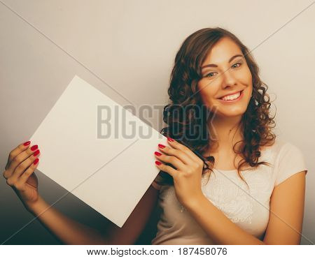 Smiling young casual style woman showing blank signboard, over grey  background isolated