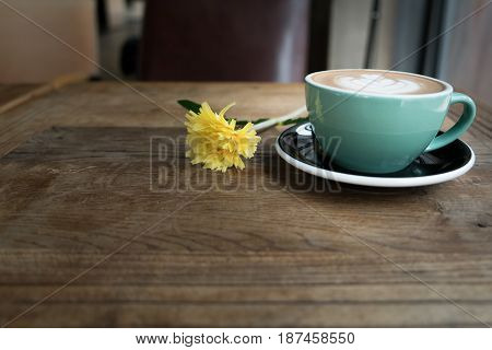 Hot Mocha Coffe Or Capuchino In The Green Cup With Heart Pattern And Yellow Flower On The Wooden Tab