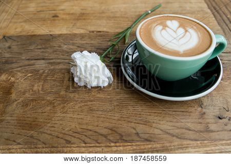 Hot Mocha Coffe Or Capuchino In The Green Cup With Heart Pattern And White Carnation On The Wooden T