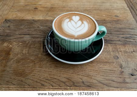 Hot Mocha Coffe Or Capuchino In The Green Cup With Heart Pattern On The Wooden Table