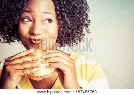Beautiful black woman eating hamburger