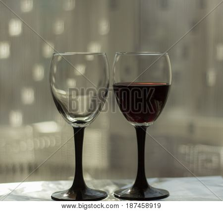Two glasses are empty and with red wineTwo glasses are empty and with red wine
