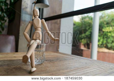 wood man is sitting cross-leg on a glass of water