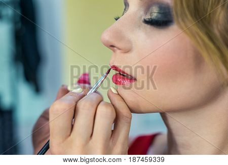close up view of Make-up artist painting red lips makeup to beautiful young girl in the studio. Red lipctick painting