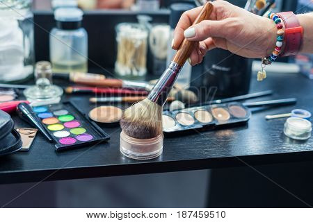Table of professional visagiste with brushes for make up and instruments for visage. Makeup kit