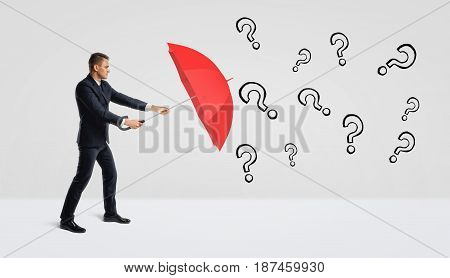 A businessman covering himself with an open red umbrella from many black drawn question marks. Business problems. Trouble at work. Choosing the best answer.