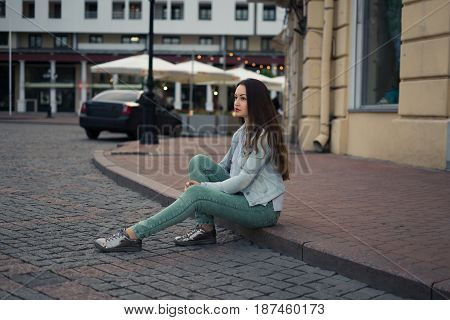 Beautiful girl sitting on a city street on curbing and looking forward. She has silver shoes