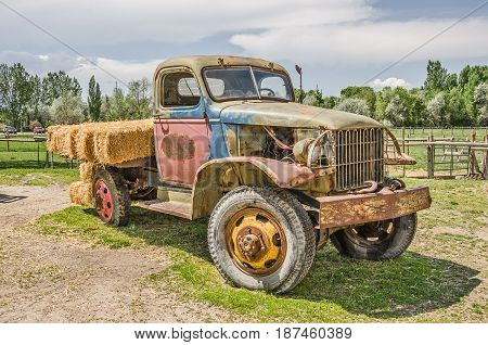 Vintage truck sporting multiple colors and a load of fresh hay