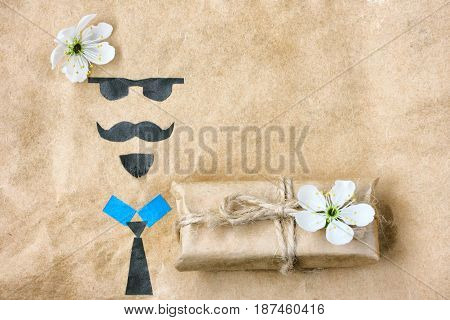 Father's day greeting card applique face with glasses mustache and beard gift box with flower on crumpled kraft paper