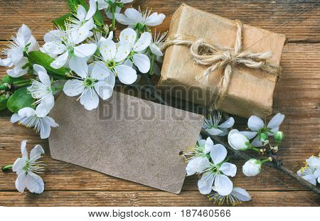 gift box empty paper tag and a branch of blossoming plum on a wooden table close-up