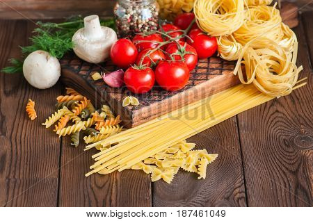 Set of ingredients for italian dinner. Assortment of raw types and shapes of pasta tomatoes cherry mushrooms garlic spices herbs on a wooden background. Close up. Top view and copy space.