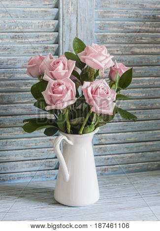 Pink roses in white enamel jug on a wooden rustic background