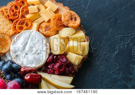 Cheese plate grape salted craker cookies dry dates cranberry fig pear pretzels on a wooden board on a black slate background.
