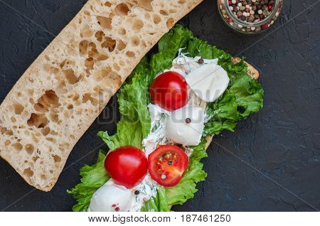 Сiabatta Sandwich With Cherry Tomatoes Mozzarella Lettuce Salad Leaf Sour Cream Sauce On Black Slate