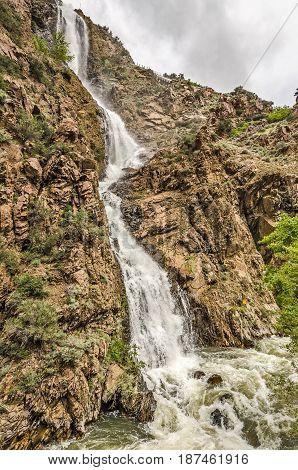 High steep waterfall rushing to a river below