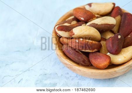 Close Up Of Brasil Nuts In A Wooden Plate On White Background