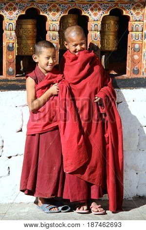 PARO BHUTAN - NOVEMBER062012 : Unidentified smiling young monks standing by the religious prayer wheels at Paro Rinpung dzong Paro Bhutan