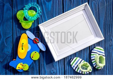 baby shower modern design with frame, shoes and toys on blue wooden background top view mock-up