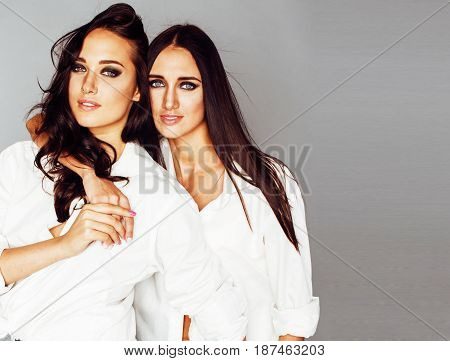 two sisters twins posing, making photo selfie, dressed same white shirt, diverse hairstyle friends smiling close up