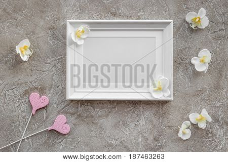 presents set for baby shower with orchid flower and frame on gray stone background top view mockup