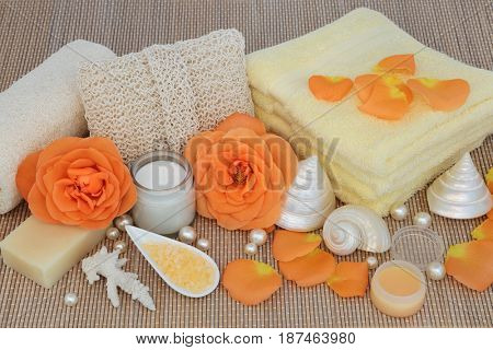Rose spa beauty treatment products and natural cleansing ingredients with seashells and pearls on bamboo background.