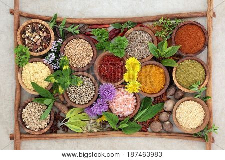 Herb and spice seasoning in wooden bowls with cinnamon sticks forming a background border on hemp paper, high in antioxidants and vitamins.
