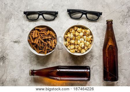 cinema and TV whatching with beer, crumbs and pop corn on stone background top view