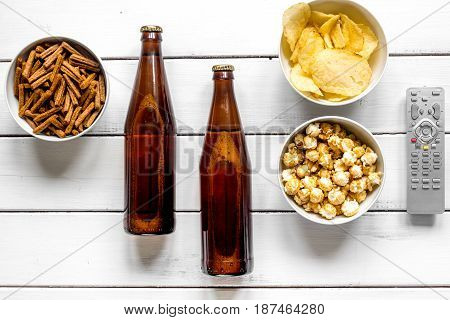 cinema and TV whatching with beer, crumbs, chips and pop corn on white wooden background top view