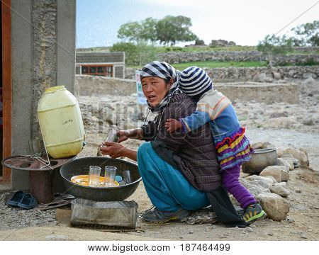 Tibetan Woman With Her Son At A Village