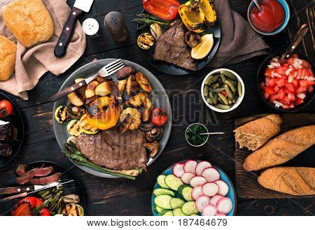 Different food cooked on the grill grilled steak and grilled vegetables on dark wooden table. Top view