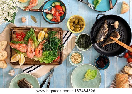 Top view family dinner table with shrimp fish grilled salad different snacks