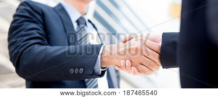 Businessman making handshake with a businesswoman panoramic banner