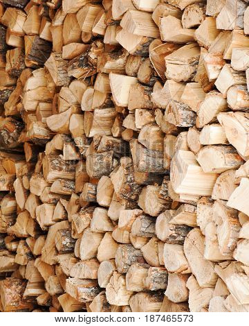 Dry chopped firewood logs in a pile. Nature abstract background with stack of firewood.