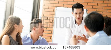 Young casual Asian businessman as a meeting leader presenting his work to mixed race colleagues panoramic banner