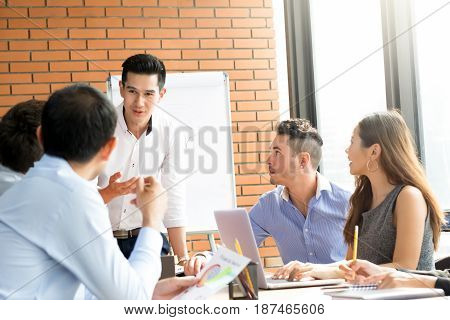 Young casual Asian businessman as a meeting leader presenting his work to mixed race colleagues