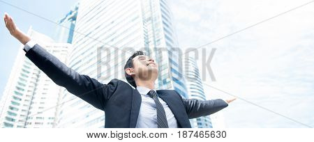 Businessman raising his arms open palms with face looking up to the sky - happy success and achievement concepts panoramic banner