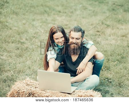 girl or happy woman and bearded man hipster with beard with long hair using laptop on hay bale on grass on summer day on natural background. Couple in love. Technology nature