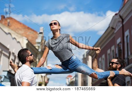 woman or sexy girl stylish fit model in sunglasses and blue jeans sitting leg split on shoulders of two bearded handsome men on sunny summer day on city street. Active lifestyle friends