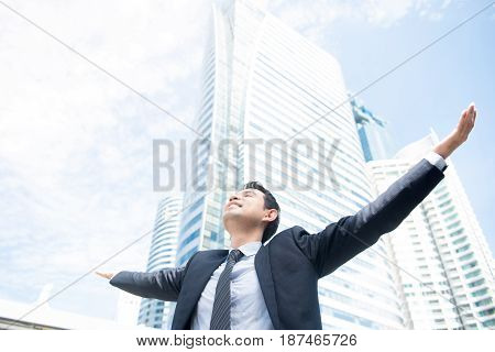 Businessman raising his arms open palms with face looking up to the sky - happy success and achievement concepts
