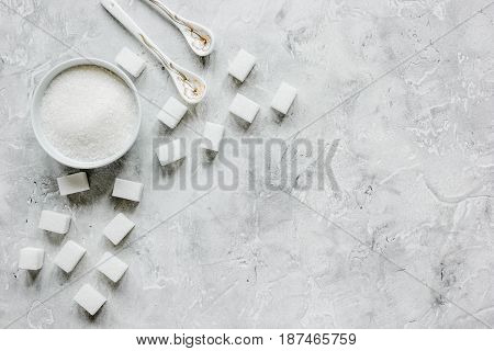 lumps of white sugar on gray kitchen table background top view mock up