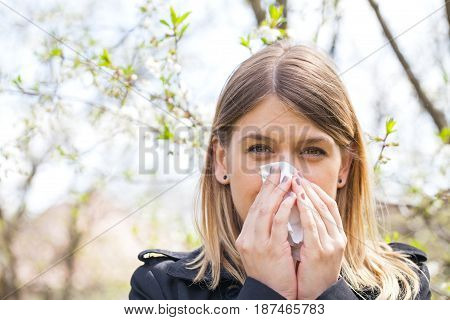 Young woman with allergy symptoms sneezing blowing her nose springtime