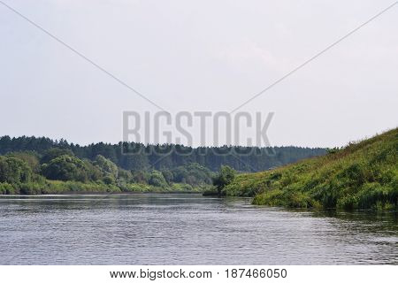 A calm dark river in a fog surrounded by green trees