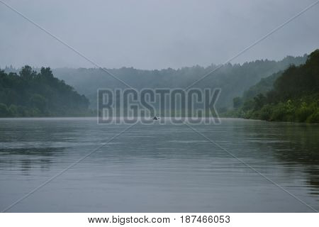 A calm dark river in a fog surrounded by green trees ahead of the boat floats