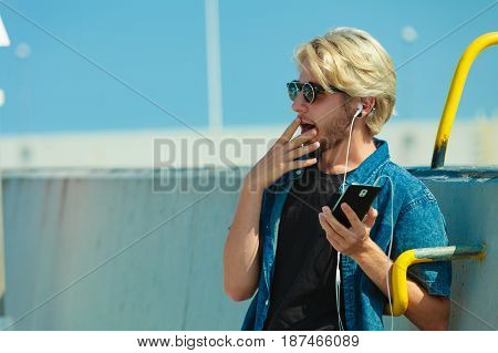 Vacation relaxation passion concept. Young fashionable blonde in sunglasses man relaxing listening to music on smartphone and enjoying beautiful sunny weather. Outdoor shot