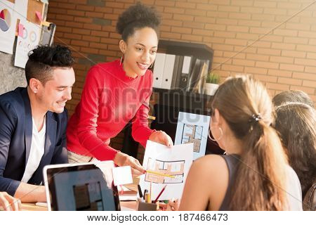 Mixed race interior designer team discussing work in the meeting